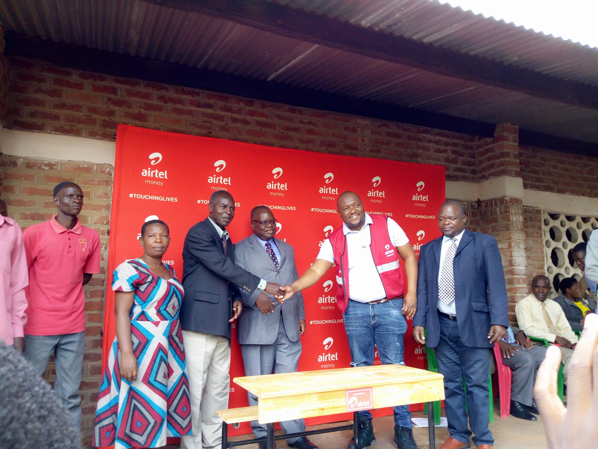 Airtel Malawi Zonal Business Manager Leslie Tsilizani offically handing over desks to Headmaster Dyton Malizani as other look on